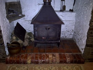 The existing stove - A very old Yeoman Woodburner. Very inefficient Solid doors The chimney is not lined and has caught fire in the past.